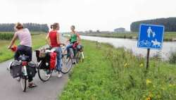 Belgian cyclists on a canal side track between Bruges and Ghent